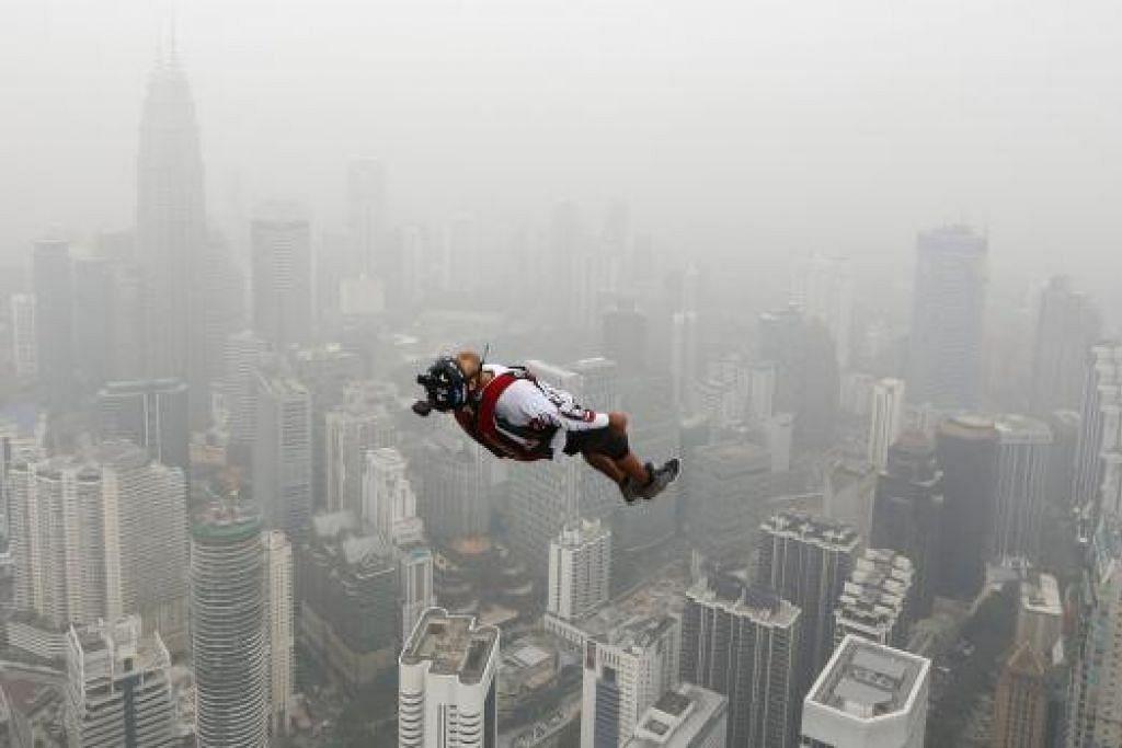 TERJUN WALAU JEREBU: Seorang peserta Lompat Menara Antarabangsa tetap meneruskan acara di Menara Kuala Lumpur dalam keadaan cuaca yang berjerebu, semalam. - Foto REUTERS