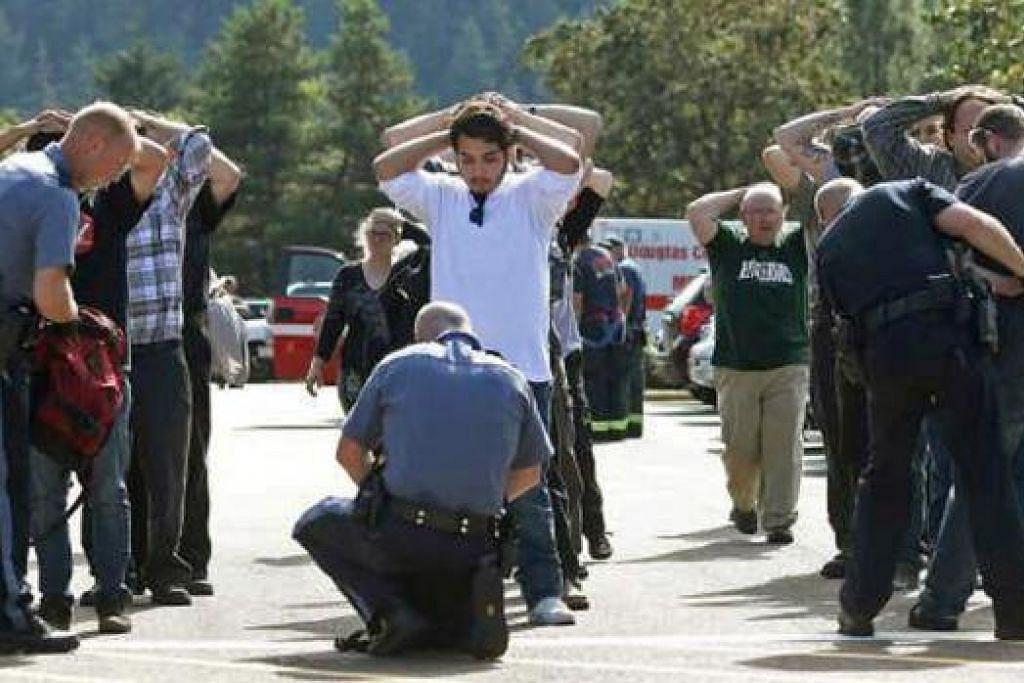 KEJADIAN KEJUTKAN MASYARAKAT SETEMPAT: Polis memeriksa beg pelajar selepas insiden tembakan itu. - Foto-foto AFP