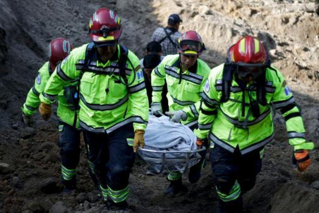 USAHA MENYELAMAT: Pasukan penyelamat membawa keluar mayat dari tapak kejadian. - Foto REUTERS