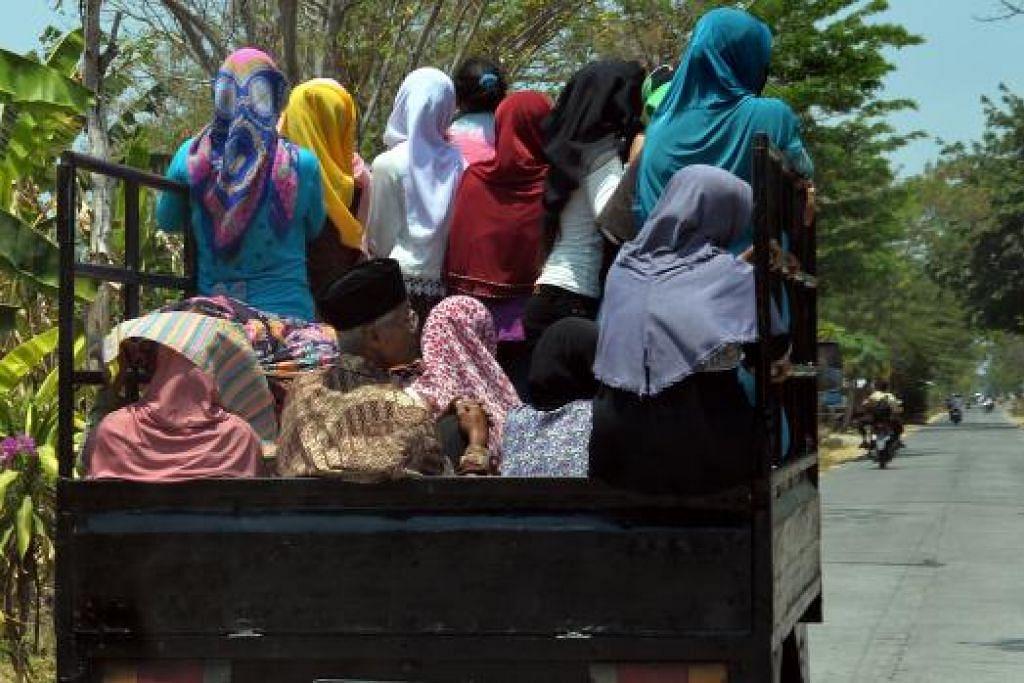 DARI JAUH MEREKA DATANG: Penduduk dari dalam dan luar Semarang datang dengan pelbagai kenderaan termasuk lori bagi mengambil agihan daging korban.