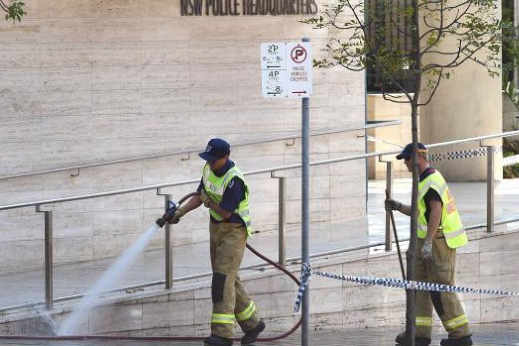 BERSIHKAN TAPAK KEJADIAN: Dua anggota bomba sedang membersihkan tapak kejadian di Sydney yang membabitkan seorang remaja lelaki membunuh seorang pegawai polis awam sebelum dia dibunuh pihak polis. - Foto AFP