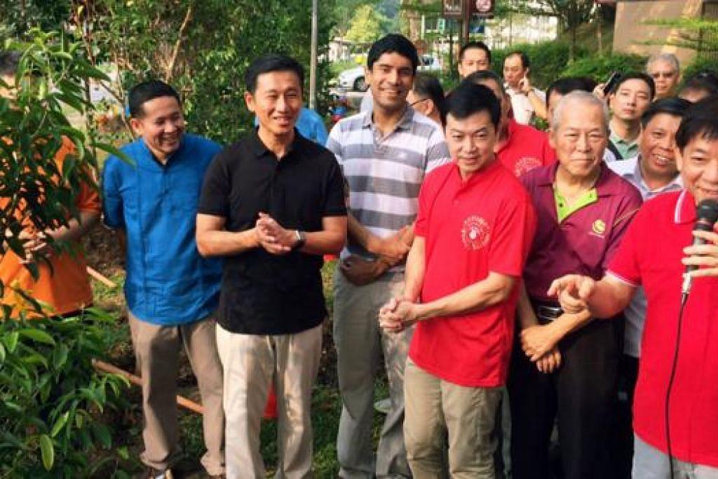 SEKITARAN MENGHIJAU: AP GRC Sembawang (dari kiri) Encik Amrin Amin (berbaju biru), Encik Ong Ye Kung, Encik Vikram Nair, Dr Lim Wee Kiak dan Encik Khaw Boon Wan (memegang mikrofon) menyertai para penduduk dalam acara menanam pokok sebagai sebahagian daripada kempen Clean and Green Singapore 2015. - Foto HAIRIANTO DIMAN