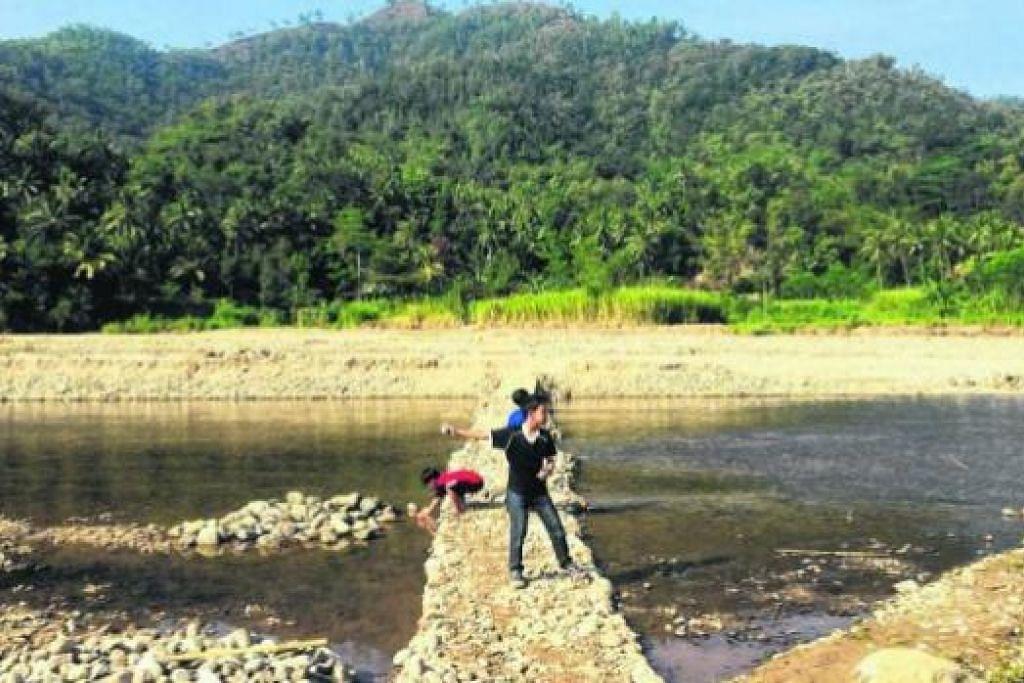 TENANG DAN DAMAI: Inilah pemandangan di tepi sungai di Kampong Kebondalem, Pacitan, yang dipenuhi batu-batu yang cukup menarik. - Foto-foto SHAHRIN DURIAT dan NURUL SYAHIRAH RAZALI