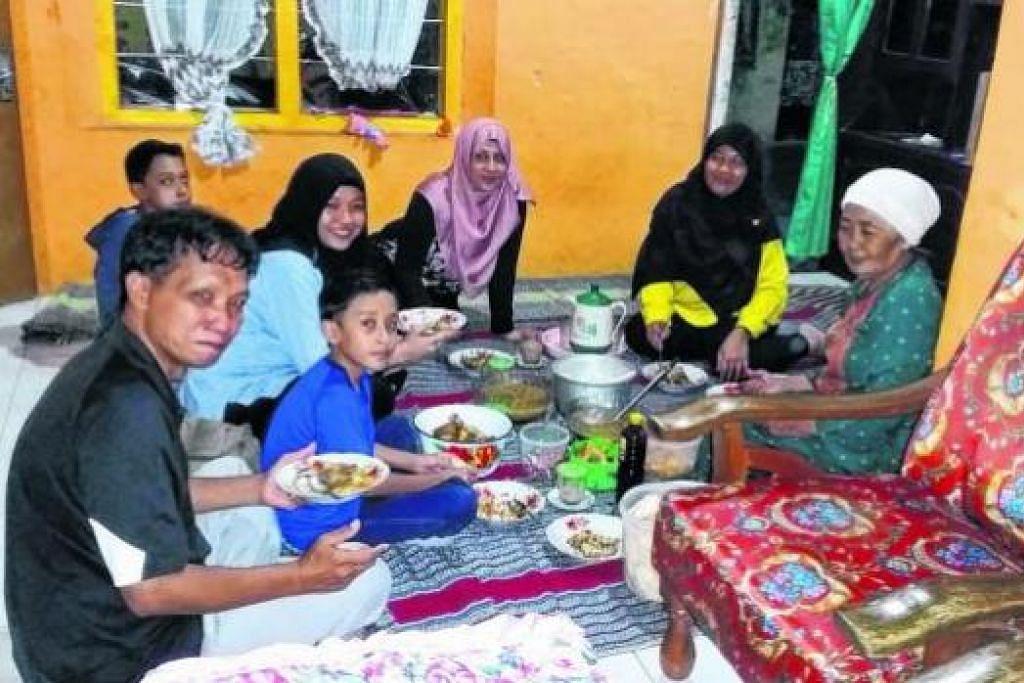 NIKMATI MAKANAN KAMPUNG: Keluarga penulis menikmati makanan kampung seperti pecel lele dan soto ayam di rumah sepupu, Cik Siti Aminah Mosman (kanan).