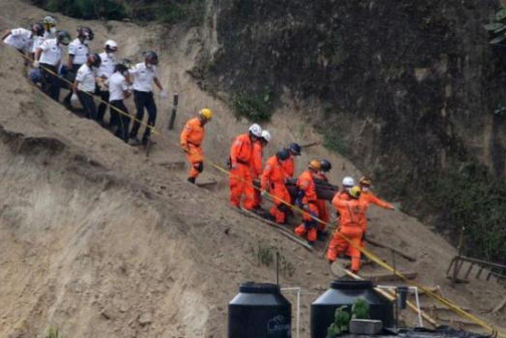 MENGELUARKAN MANGSA YANG TERTIMBUS: Pasukan penyelamat membawa mayat penduduk kampung di Santa Catarina Pinula yang dapat digali keluar ekoran kejadian tanah runtuh yang berlaku kelmarin. Ramai saudara-mara yang hampir berputus asa tidak dapat menemui banyak lagi mangsa yang tertimbus dalam bencana alam itu. - Foto REUTERS