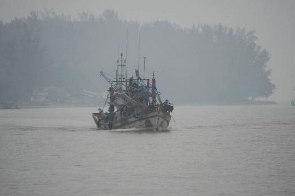 Sebuah bot nelayan belayar dalam keadaan berjerebu di Sungai Narathiwat di wilayah Narathiwat di selatan Thailand pada Isnin, 5 Oktober. Gambar AFP