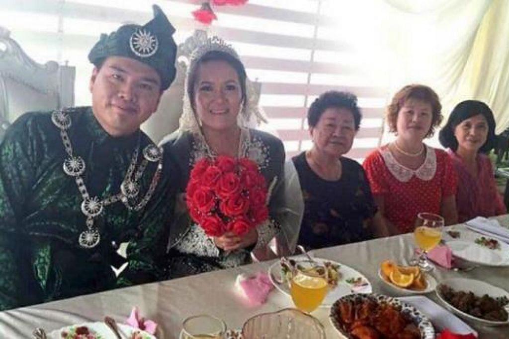 CARA MELAYU: Cik Siau Hooi dan suaminya, Encik Lim Choon Yong, segak dengan pakaian pengantin Melayu ketika majlis perkahwinan mereka diadakan di Kampung Tebuk Haji Musa, Parit Buntar, Ahad. - Foto THE STAR
