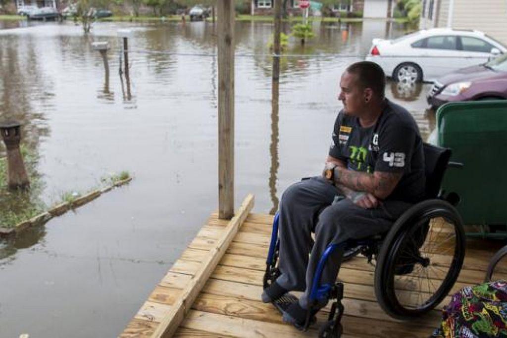 DITENGGELAMI AIR: Encik Chris Stubo melihat air naik di sekeliling rumahnya di Appllewood Court, South Carolina, kelmarin. - Foto REUTERS