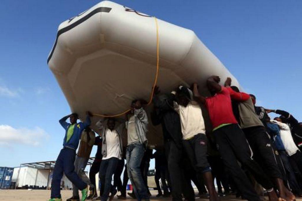 MUJUR SELAMAT: Beberapa pelarian mengangkat rakit keselamatan yang digunakan oleh pengawal pantai Libya bagi menyelamatkan mereka di pangkalan tentera laut dekat Tripoli, Libya. - Foto AFP