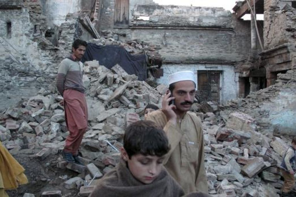 HADAPI MUSIBAH: Penduduk melewati sebuah rumah yang runtuh akibat gempa bumi di  Mingora, Swat, Pakistan. - Foto REUTERS