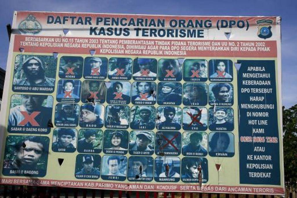 PENGGANAS DIKEHENDAKI: Papan tanda yang dipasang polis Indonesia yang memaparkan wajah dan nama para individu, termasuk pengganas paling dikehendaki, Santoso, yang terlibat dalam kes-kes terorisme di Poso, Sulawesi Tengah. - Foto REUTERS