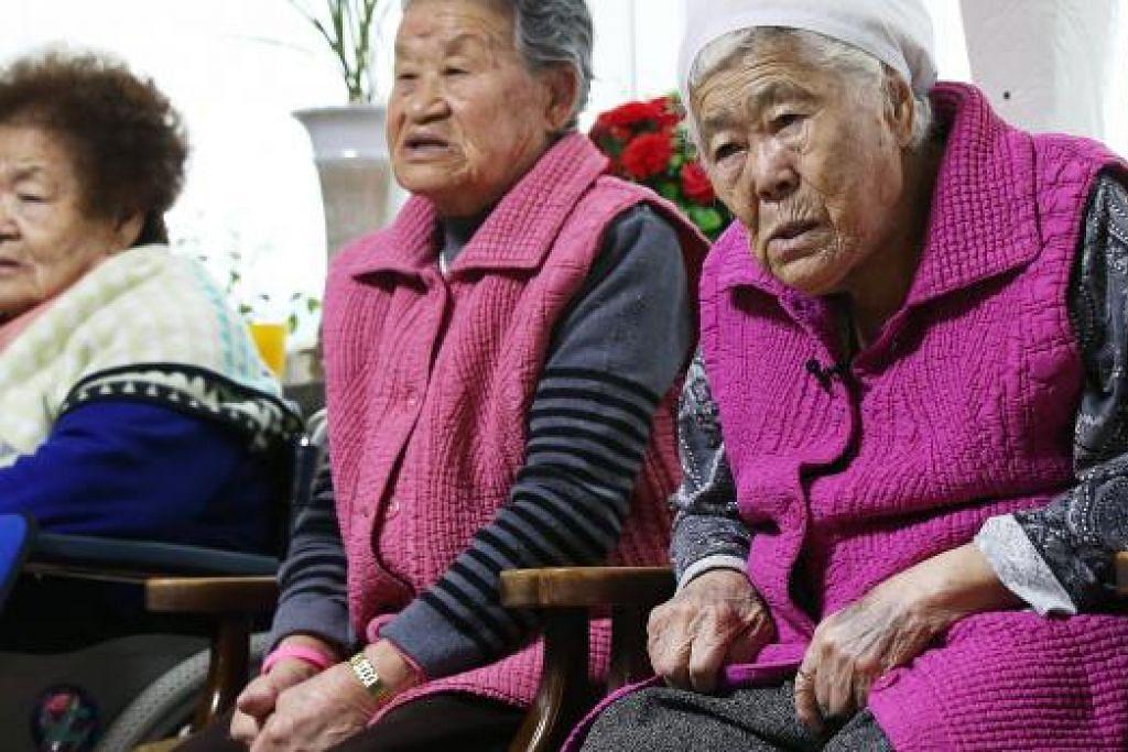 TERIMA PAMPASAN: Bekas hamba seks warga Korea Selatan kelihatan sedang menonton laporan berita pada 28 Disember lalu sedang mereka menanti keputusan pertemuan antara menteri ehwal luar Korea Selatan dan Jepun di Gwangju, Korea Selatan, berhubung isu pampasan untuk mereka atas apa yang berlaku sewaktu Perang Dunia ke-2 dahulu. - Foto REUTERS