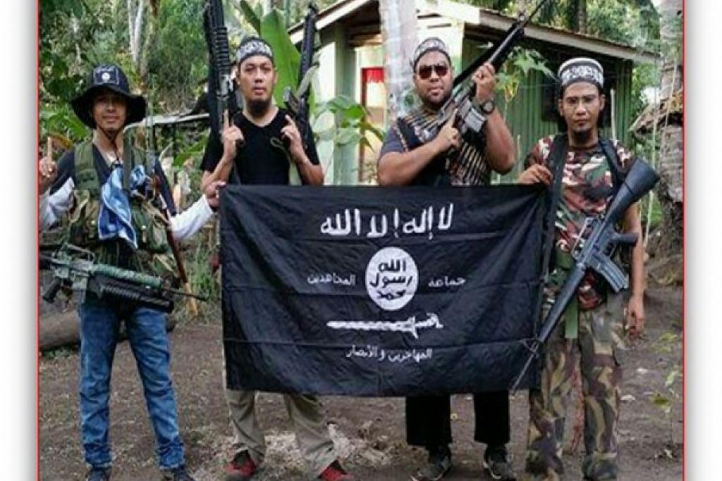 """(Dari kiri) Seorang pejuang Abu Sayyaf dan militan Malaysia, Mahmud Ahmad, Muhammad Joraimee Awang Raimee dan Muammar Gaddafi, bergambar dengan bendera ISIS. Militan Malaysia yang bersembunyi di selatan Filipina dipercayai merancang membentuk puak """"rasmi""""  ISIS di Asia Tenggara dengan mengumpulkan kumpulan pengganas di Malaysia, Indonesia dan Filipina, termasuk Jemaah Islamiah dan Abu Sayyaf."""