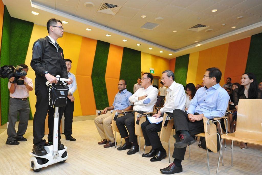 GUNA TEKNOLOGI: Encik Melvin Chong, pegawai keselamatan bersama Reachfield Security and Safety Management Pte Ltd, menunjukkan cara menggunakan segway kepada Encik Sam Tan (dua dari kanan). – Foto THE STRAITS TIMES