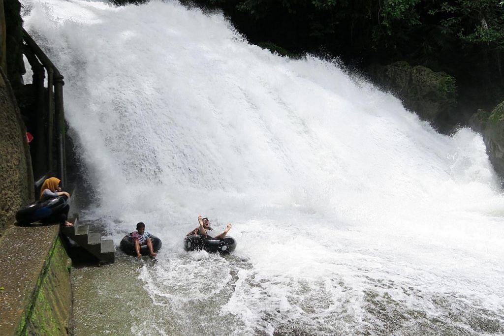 SERONOK MAIN AIR: Pengunjung air terjun di Taman Wisata Alam Bantimurung berani meluncur turun menggunakan boya walaupun airnya sangat deras.