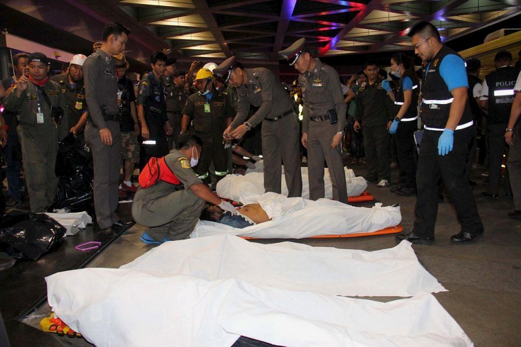 MALANG TAK BERBAU: Anggota polis dan anggota penyelamat melihat mayat mangsa selepas kemalangan yang mungkin disebabkan oleh pelepasan bahan kimia melawan api secara tidak sengaja oleh pekerja penyenggara di ibu pejabat bank terbesar Thailand, Siam Commercial Bank, di Bangkok. - Foto