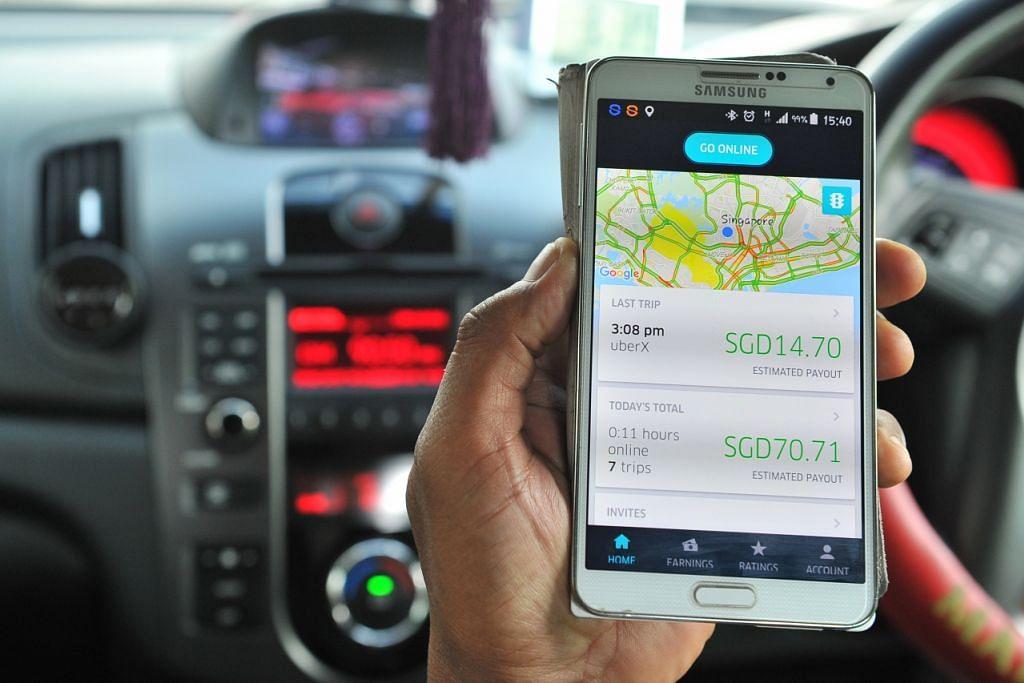 Seorang pemandu menunjukkan aplikasi pemandu Uber di telefon bimbitnya.