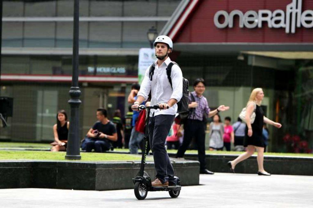 Seorang lelaki menunggang e-skuter boleh lipat.