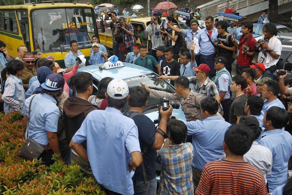Sebuah teksi dihalang bergerak kerana tidak mengambil bahagian dalam bantahan oleh pemandu teksi di Jakarta yang menuntut pemerintah Indonesia mengharamkan aplikasi sewa kereta private.