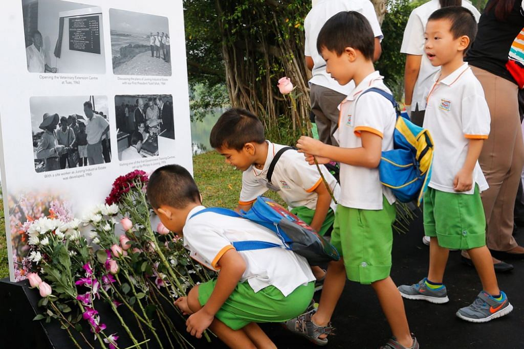 ACARA DI SERATA PULAU - SI KECIL JUGA KENANG JASA: Kanak-kanak ini meletakkan bunga di depan gambar mendiang Encik Lee Kuan Yew di Taman Tasik Jurong semalam. - Foto THE STRAITS TIMES