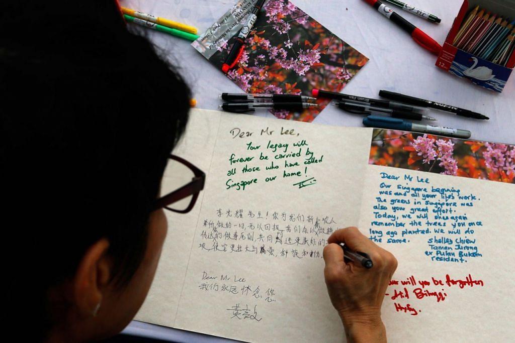 ACARA DI SERATA PULAU - CATATKAN PENGHARGAAN: Salah seorang penduduk Jurong meluahkan rasa terima kasih kepada mendiang Encik Lee Kuan Yew. - Foto THE STRAITS TIMES