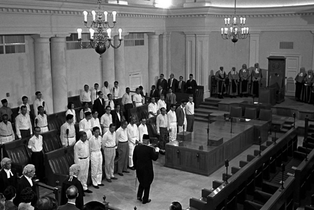 SESI PARLIMEN BERLANGSUNG: Bentara Cokmar Encik Mahmood Abdul Wahab membawa cokmar semasa memimpin perarakan Speaker di pembukaan parlimen pertama Singapura pada 8 Disember 1965.