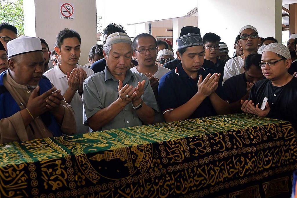 HIBA ATAS PEMERGIAN ANAK: Ayah Allahyarham Nasrulhudin (depan, berbaju kelabu) sedang berdoa bersama hadirin lain di kolong blok di Tampines. - Foto-foto KHALID BABA