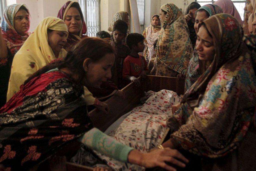 Saudara-mara menengisi pemergiaan seorang korban serangan di Lahore, Pakistan pada Ahad (27 Mac)