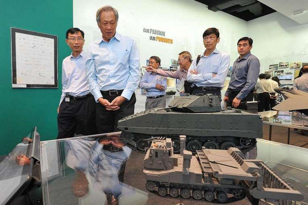 Dr Ng (dua dari kiri) meninjau model kenderaan pertempuran dan antiperiuk api di Galeri DSTA di Kompleks Bersepadu DSTA semasa merasmikan kompleks itu pada Selasa (29 Mac).