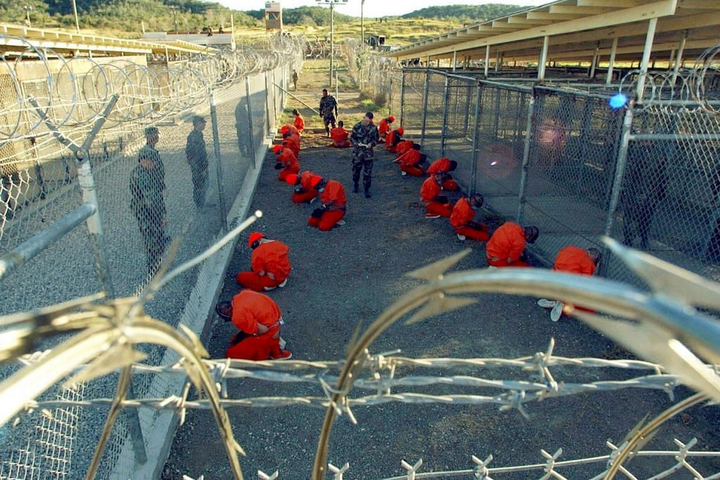 Gambar fail 2002 ini menunjukkan tahanan dalam jumpsut oren duduk di sebuah kawasan tahanan sementara dengan diperhatikan polis tentera Amerika di Kem X-Ray sementara, yang kemudian ditutup dan digantikan dengan Kem Delta, di Pangkalan Tentera Laut Amerika di Teluk Guantanamo di Cuba. Layanan ke atas tahanan di penjara itu menarik kritikan antarabangsa dan membuat Amerika dituduh melakukan penyeksaan.