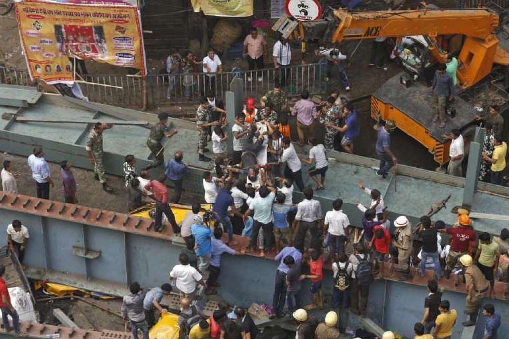 Pekerja penyelamat membawa mangsa yang cedera dari tapak sebuah jejambat dalam pembinaan yang runtuh di Kolkata.