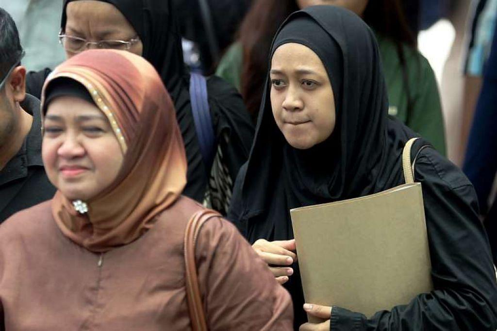 Cik Nurul Asyikin (belakang), bersama ibunya, Cik Juraidah Nabi, menggunakan selimut untuk memadamkan api yang menyelubungi suami beliau, Allahyarham Mohd Rizalludin Hassan.