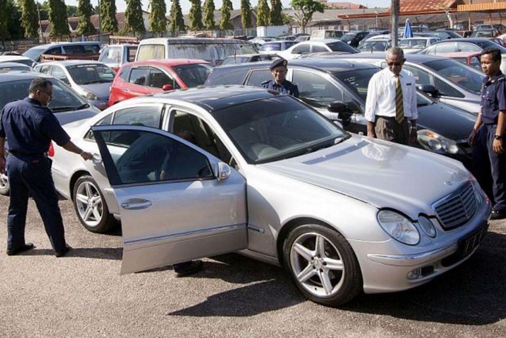 Pegawai memeriksa kereta 'klon' mewah dari Singapura yang dirampas pihak berkuasa Johor Januari lalu.