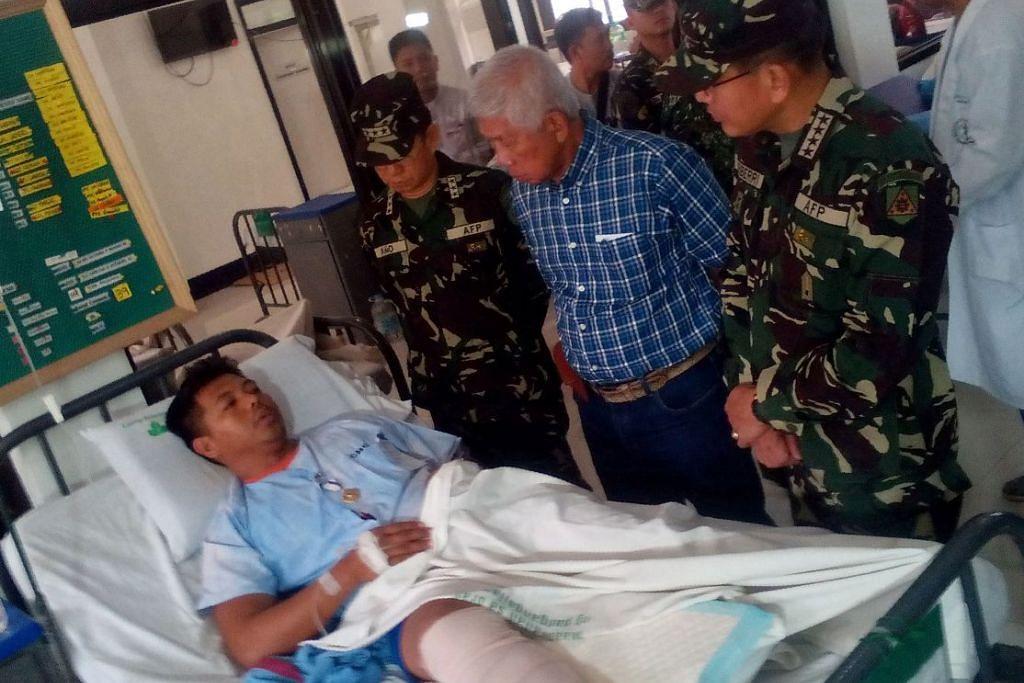 Setiausaha Pertahanan Filipina, Encik Voltaire Gazmin (dia dari kanan) dan Jeneral Hernando Iriberri (kanan) melawat salah seorang daripada 53 askar yang cedera di sebuah hospital tentera di Zamboanga di  Mindanao pada Ahad (10 April), sehari selepas tentera bertempur dengan militan kumpulan Abu Sayyaf.