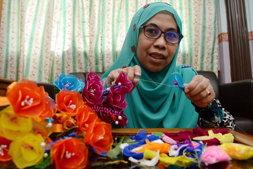 SEBAK MASIH TERASA: Cik Salmah Abdullah meluangkan masa menggubah bunga yang diperbuat daripada kain, sepanjang menjaga suaminya, Allahyarham Azman Ahmad menderita barah otak di Hospital Bright Vision. – Foto TAUFIK A. KADER