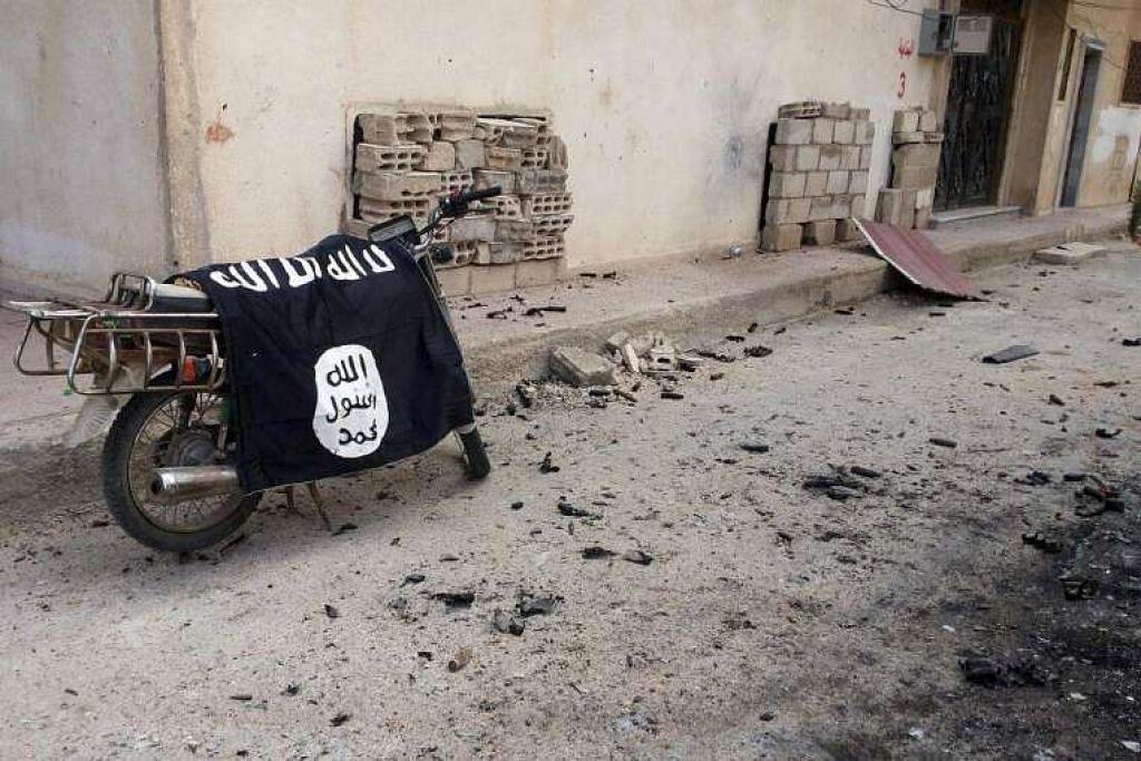Bendera kumpulan militan ISIS dibiarkan pada sebuah motosikal di Palmyra, Syria.