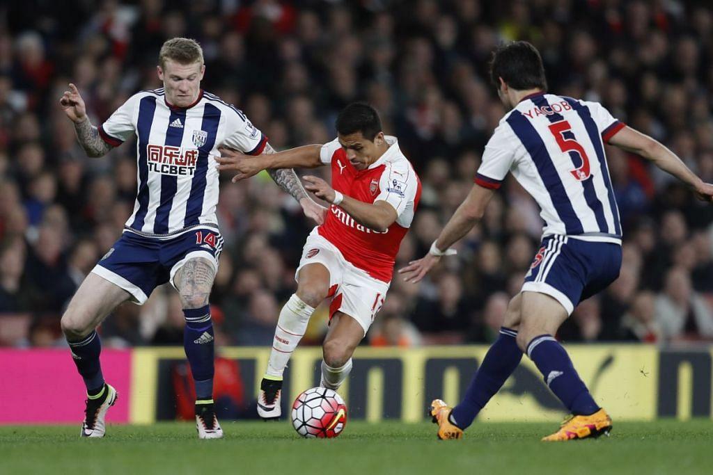 Pemain Arsenal, Alexis Sanchez (tengah), menghadapi pemain West Bromwich Albion, James McClean dan Claudio Yacob, dalam perlawanan EPL di Stadium Emirate pada Khamis (21 Apr).
