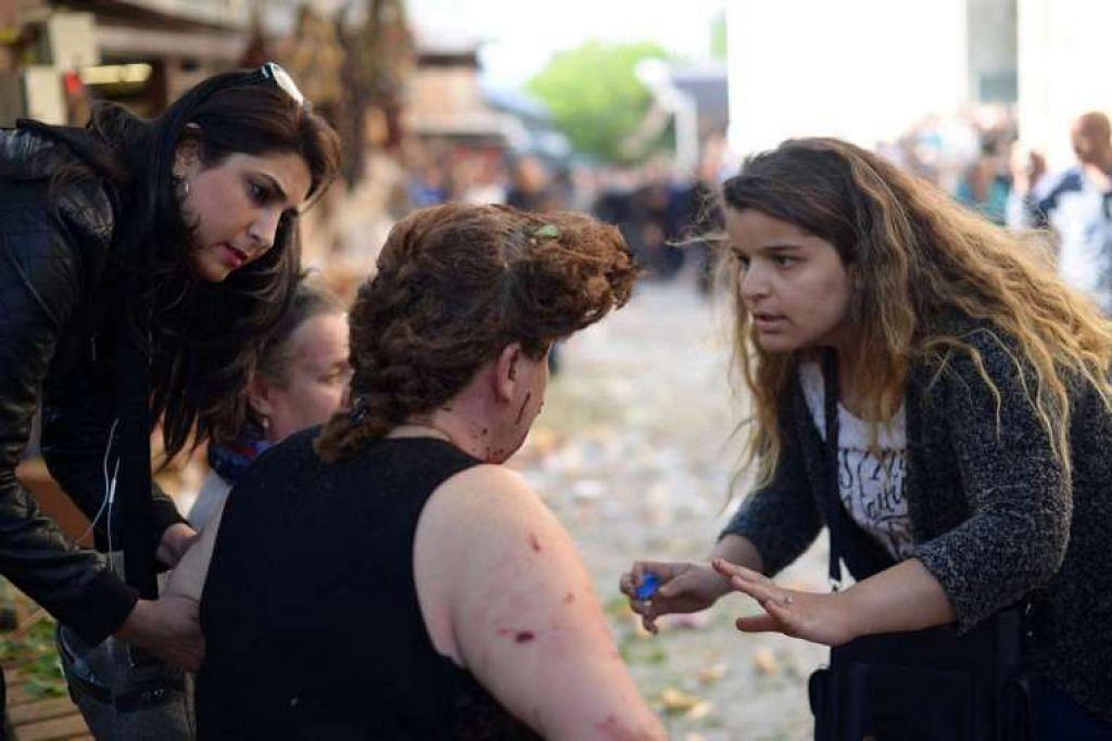Seorang wanita memberi pertolongan cemas kepada seorang wanita yang cedera berikutan pengeboman di Bursa, Turkey, pada Rabu (27 April 2016).