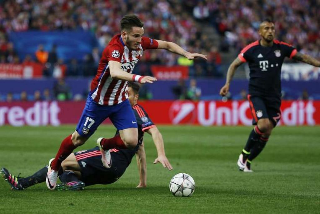 Saul Niguez bergerak melepasi pemain Bayern Munich Xabi Alonso sebelum menjaringkan gol bagi Atletico Madrid.