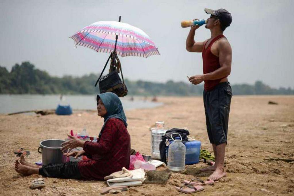 Seorang lelaki minum air di tebing Sungai Pahang yang kering.