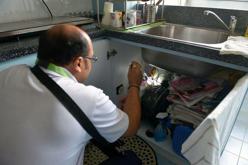 Seorang pegawai NEA memeriksa dalam kabinet dapur sebuah flat bagi memastikan tiada nyamuk membiak. NEA terus menegaskan bahawa pembasmian habitat pembiakan nyamuk dan menyembur racun serangga bagi mengawal populasi nyamuk dewasa masih merupakan kunci pencegahan denggi.