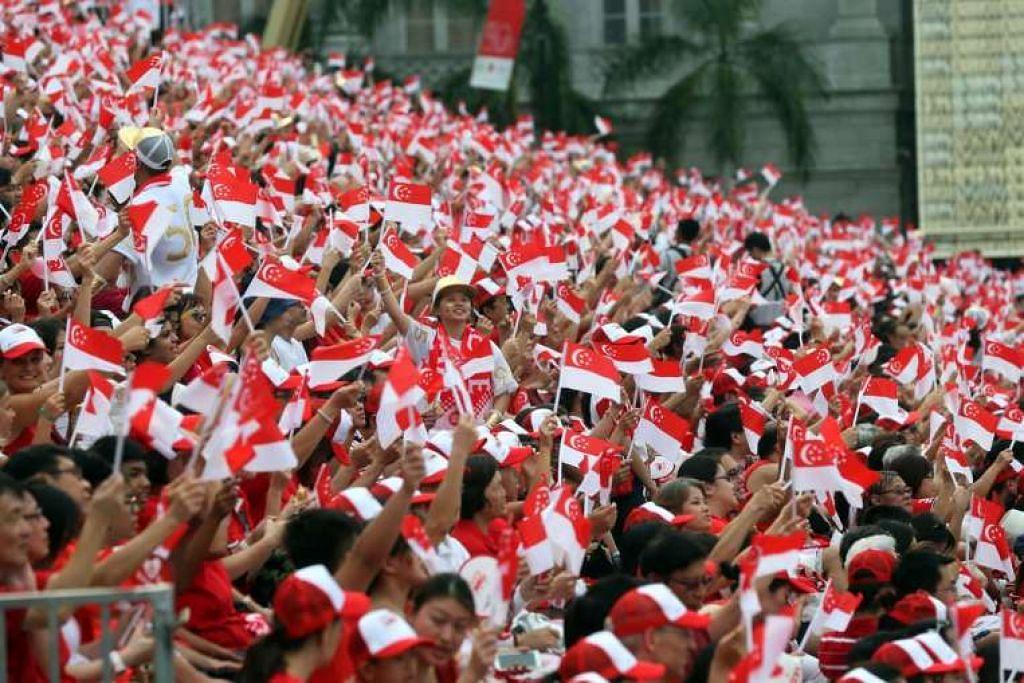 Penonton mengibarkan bendera mini Singapura semasa Perbarisan Hari Kebangsaan (NDP) Jubli Emas di Padang pada 9 Ogos 2015.