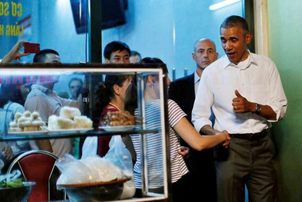 Encik Obama menunjukkan ibu jarinya selepas makan hidangan mi tepung beras bersama Encik Bourdain.