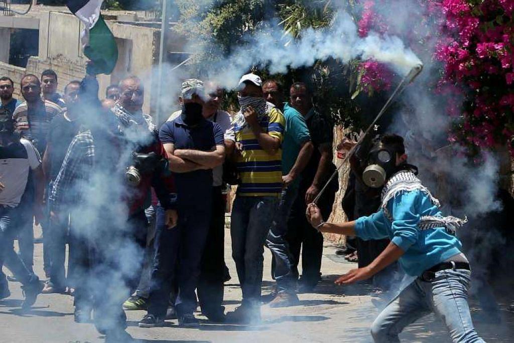 Seorang penunjuk perasaan Palestin membaling kanister gas pemedih mata kembali ke arah pasukan keselamatan Israel semasa pertempuran pada 27 Mei di kampung Kfar Qaddum di West Bank, yang diduduki Israel.