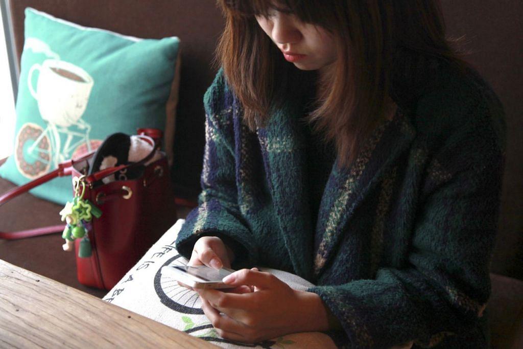 Seorang wanita menggunakan sebuah aplikasi bergerak di sebuah kafe di Beijing.