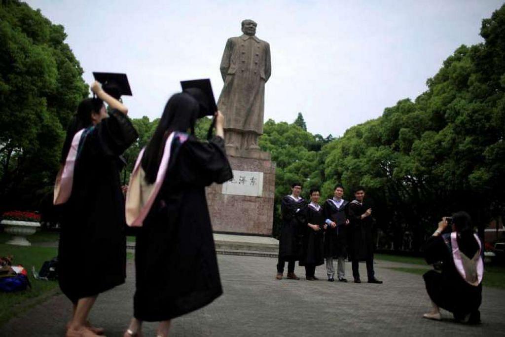 Para graduan mengambil gambar di depan patung pemimpin China, Mao Zedong, di  Universiti Fudan  di Shanghai.