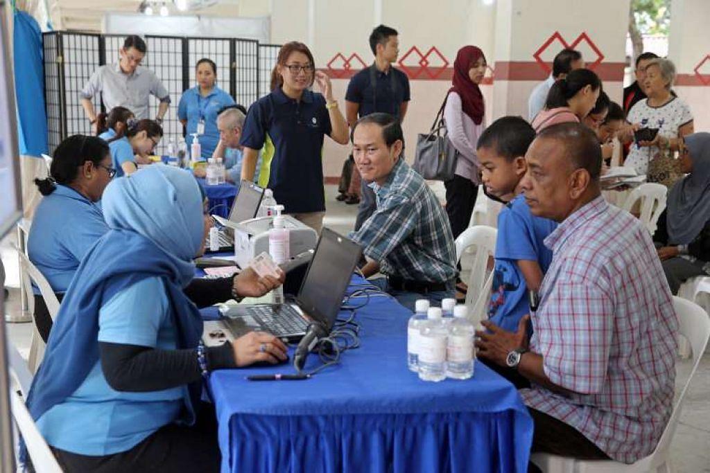 Penduduk Blok 203 Ang Mo Kio Ave 3 menjalani pemeriksaan kesihatan di kolong pada pagi Khamis (16 Jun).
