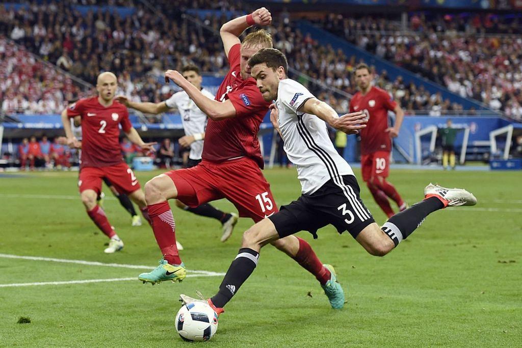 Pemain pertahanan Jerman, Jonas Hector (jeri putih) cuba membuat hantaran melepasi pemain pertahanan Poland, Kamil Glik,  semasa perlawanan Euro 2016 Kumpulan C yang berakhir dengan seri 0-0 di  Stadium Stade de France di Saint-Denis pada 16 Jun, 2016.