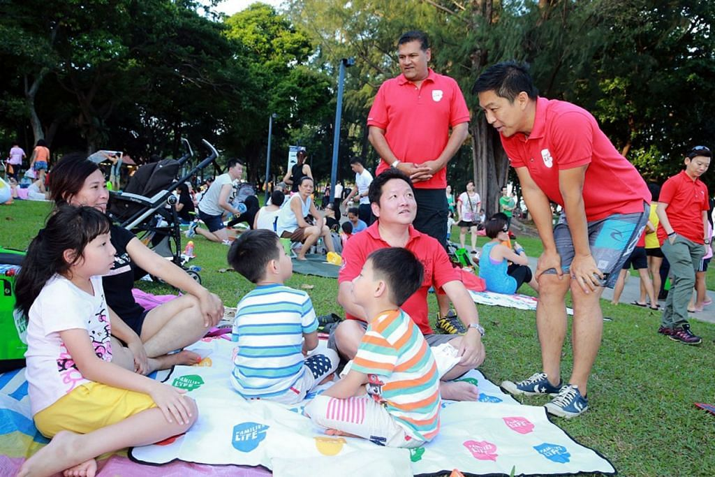 KUKUHKAN KELUARGA: Encik Tan beramah mesra dengan satu keluarga yang meluangkan masa berkhemah, bersamanya ialah BG(NS) Ishak. - Foto FAMILIES FOR LIFE