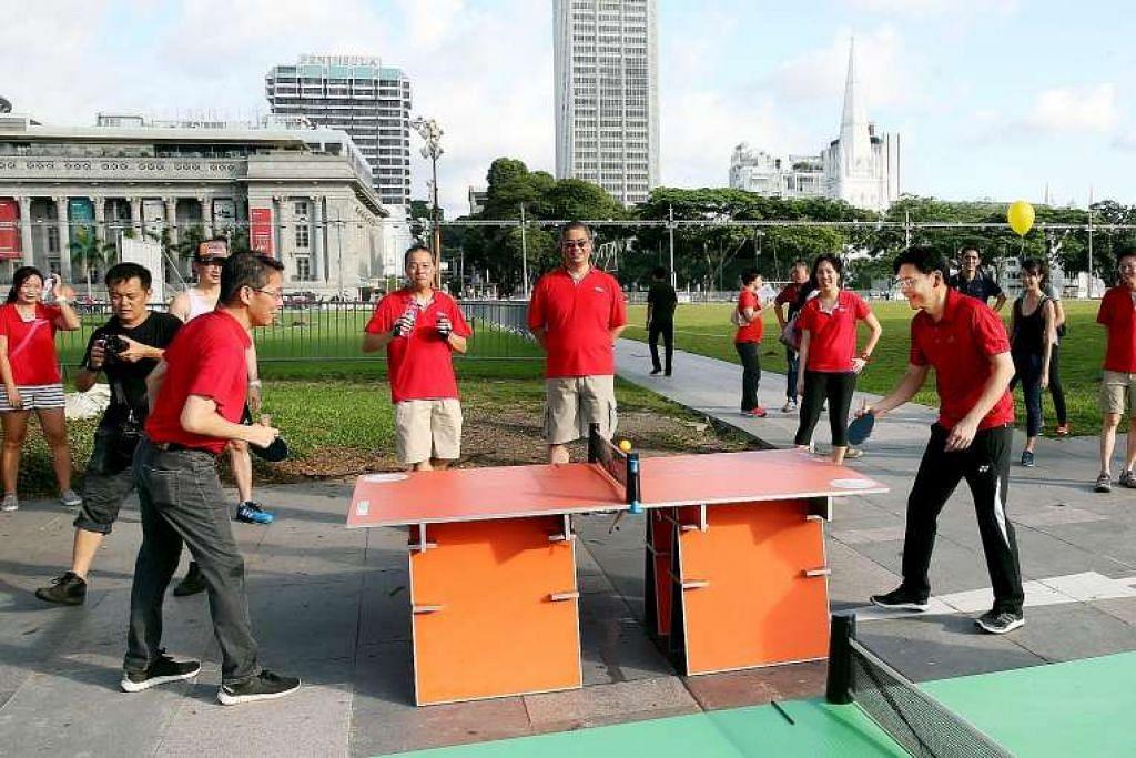 Menteri Pembangunan Negara Lawrence Wong (kanan) menikmati permainan ping pong ketika acara Ahad Bebas Kereta pada Ahad (26 Jun).